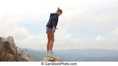 Sporty Woman Standing on Top of Rock, She Wearing Jacket and...