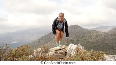 Sporty Woman Standing on Top of Rock With Hands Wide Open,...