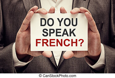 Do You Speak French. Man wearing suit holding a signboard