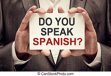 Do You Speak Spanish. Man wearing suit holding a signboard