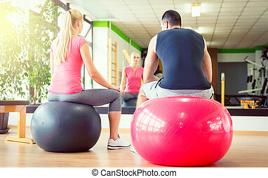 Young attractive couple ready for workout with fitball