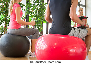 Young couple training in gym with dumbbells in front of a mirror sitting on fitballs