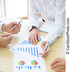 Business People Analyzing Financial Results on Graphs around...