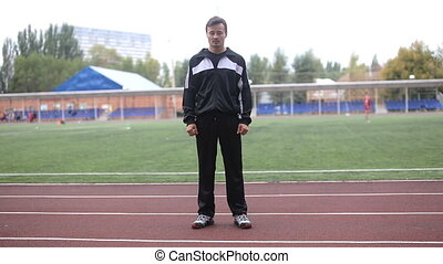 runner in the stadium is on track and looking at the camera
