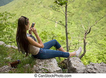 Composing - Young brunette using cellphone to take picture...