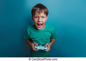 Teen boy of twelve European appearance holds a gaming...