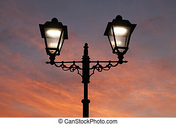 Lamppost with two lighted lanterns on a background of red...