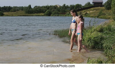 Young girls go into the water of the lake