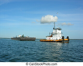 Tug Boat - Tug boat towing a barge in a calm bay with clouds...