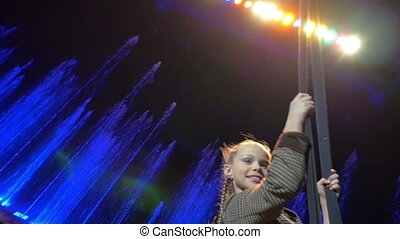 Girl swinging on the trapeze during performance