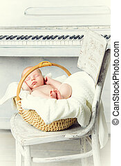 lullaby - Little newborn baby sleeps next to a white piano....