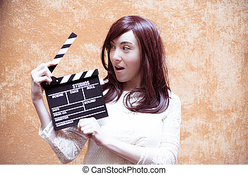 Young woman in 70s hippie style smiling with clapperboard,...