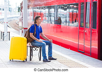 Young man with baggage at a train station near express -...