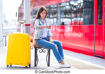 Young woman with luggage on train platform waiting for...