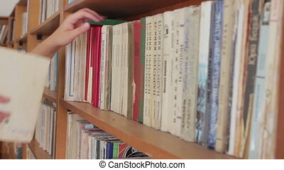 Long hall of library with wooden bookcases - Girl pulls out...