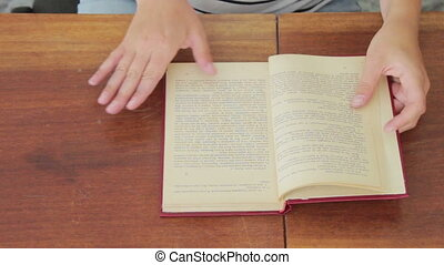 Woman leafing through a book on the table. - Girl in the...