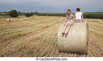 Two girl jump off the haystack. - Young happy children jump...