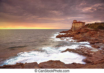 Boccale castle landmark on cliff rock and sea on warm sunset...