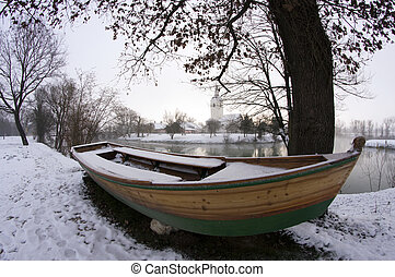 Rowing boat by the river in winter.