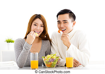 Young  smiling couple eating healthy food