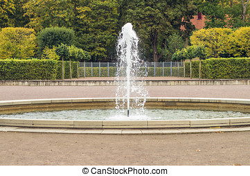 Circle fountain with colorful autumn trees on background