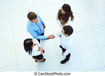 Top view of business people shaking hands, finishing up a meeting - Welcome to business