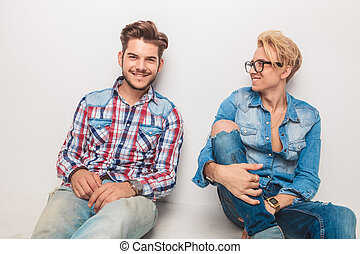 young man laughing to his friend while sitting