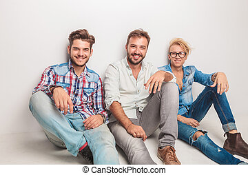 happy group of men laughing for the camera while sitting