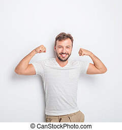 laughing young fit casual man flexing his muscles - laughing...