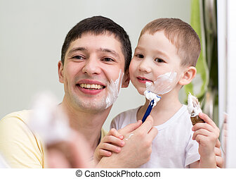 cute little boy and father shave looking at mirror in...