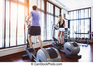 Couple training on a treadmill in a sport center