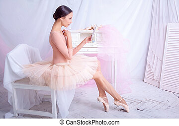 Professional ballet dancer looking in the mirror on pink -...