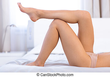 Sexy female legs on the bed - Portrait of a sexy female legs...