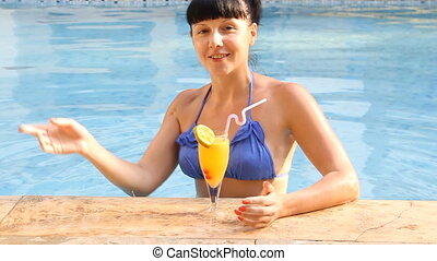 woman relaxing in swimming pool with cocktails