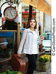 Excited girl with a suitcase and a tourist map, waiting at...