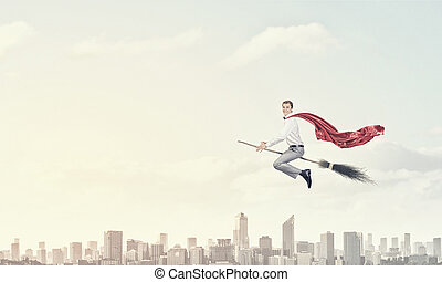 Guy on broom - Young businessman flying on broom high in sky