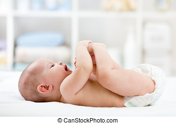 baby playing with his feet lying on bed in nursery room