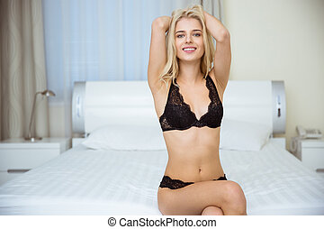 Girl in lingerie sitting on the bed - Portrait of a smiling...