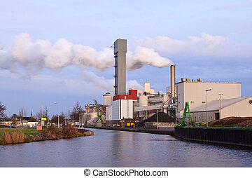 Industrial factory with smoking chimney