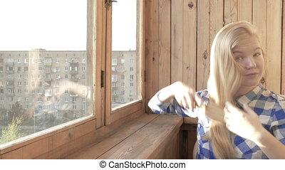 beautiful young woman brushing her hair near the window