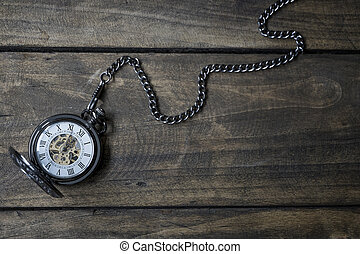 Vintage watch on a wooden background showing five to twelve.