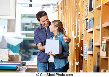 Woman Holding Gift Box While Looking At Man In Store
