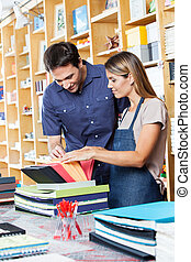 Saleswoman Assisting Male Customer To Choose Envelop - Mid...