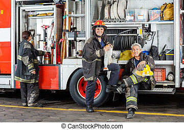 Confident Firefighters By Truck At Fire Station