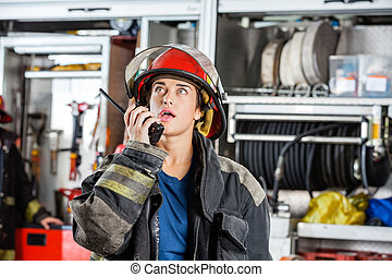 Confident Female Firefighter Using Walkie Talkie - Confident...