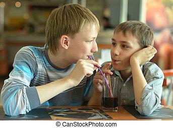 Two boys drinking coke - Two cute boys drinking coke in cafe