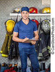Confident Firefighter Holding Clipboard At Fire Station -...