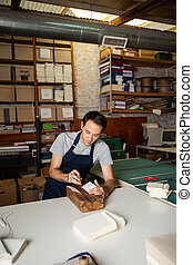 Manual Book Binding - Mid adult male worker using needle to...