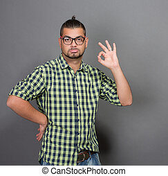 Fashionable hipster man giving okay sign in studio -...