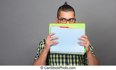 Fashionable hipster man hiding behind files in studio -...